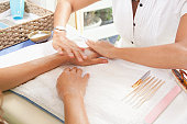 woman getting manicure at spa