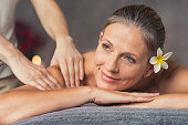 Senior woman in spa salon getting massage. Closeup of a beautiful woman during spa treatment. Beautiful mature woman receiving massage of shoulder at beauty salon.'r