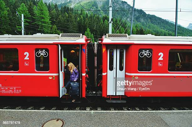 Woman Getting Off Red Train Carriage On Station