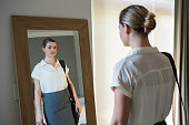 Businesswoman getting ready for office in bedroom at home