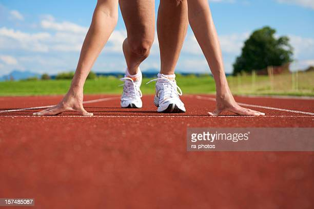 A woman getting ready to sprint on the track and field