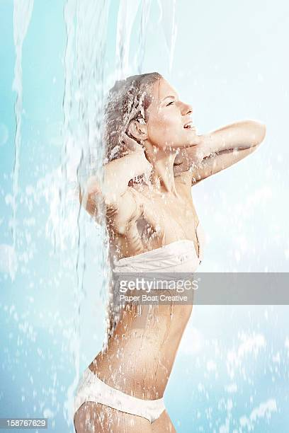 Woman getting splashed by a waterfall