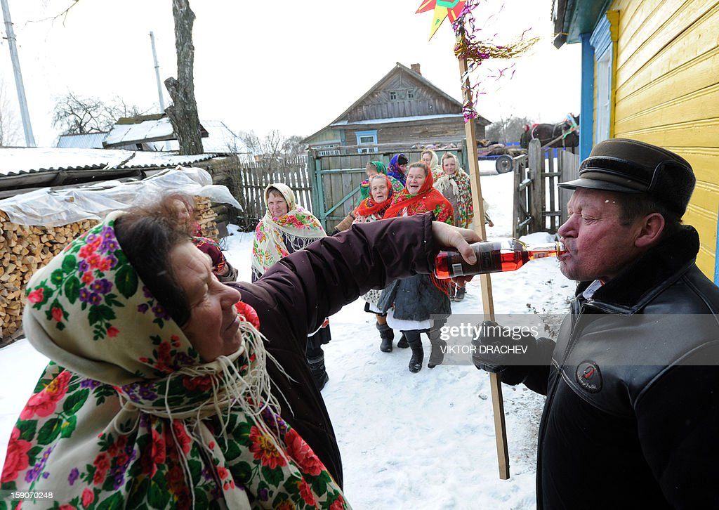 A woman gives a drink to a person as they attend Christmas celebration in the town of Richev, some 290 km south from Minsk. on January 7, 2013. Orthodox Christians celebrate Christmas on January 7 in the Middle East, Russia and other Orthodox churches that use the old Julian calendar instead of the 17th-century Gregorian calendar adopted by Catholics, Protestants, Greek Orthodox and commonly used attendsin secular life around the world.