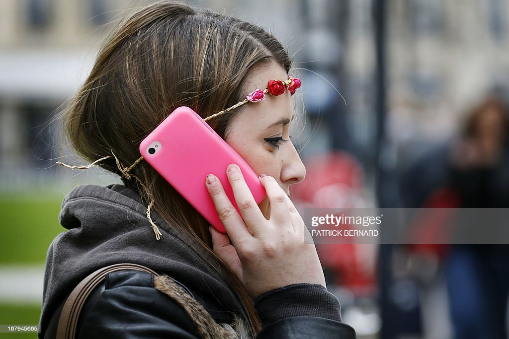 FRAYSSE - A woman gives a phone calle with a brighty colored smartphone in Bordeaux on May 3, 2013 . AFP PHOTO/PHOTO PATRICK BERNARD