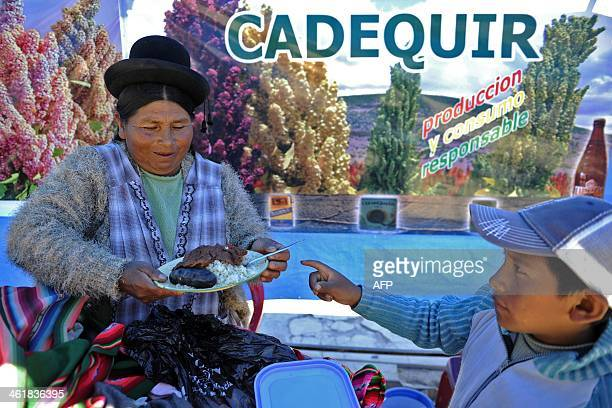A woman gives a plate of 'quinua' species of goosefoot grown as an edible crop and meat to a child in the streets of Uyuni Bolivia on January 11 2014...