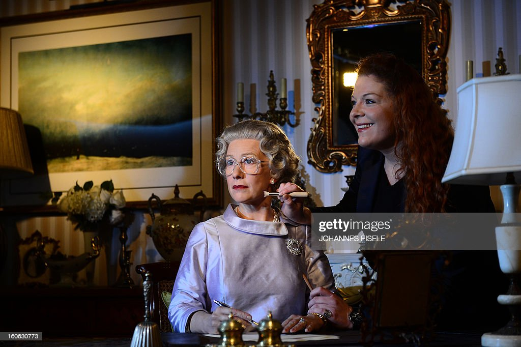 A woman gives finishing touches to a wax likeness of British actress Helen Mirren dressed as Britain's Queen Elizabeth II at Madame Tussauds wax museum in Berlin on February 4, 2013. AFP PHOTO / JOHANNES EISELE