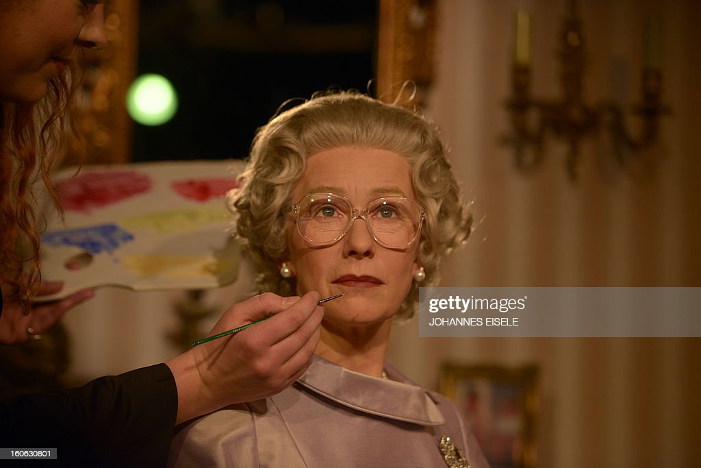A woman gives finishing touches to a wax likeness of British actress Helen Mirren dressed as Britain's Queen Elizabeth II at Madame Tussauds wax museum in Berlin on February 4, 2013.