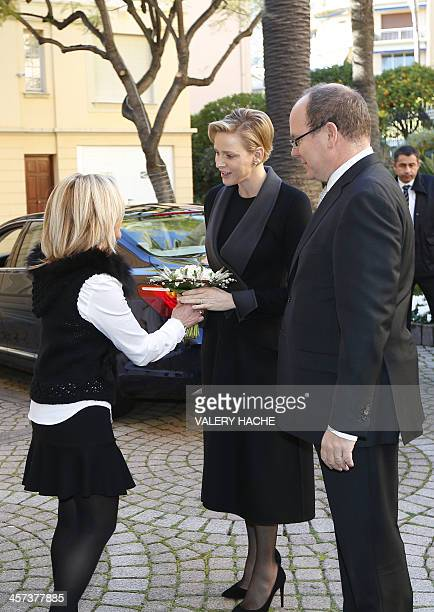 A woman gives flowers to Princess Charlene of Monaco as she arrives along with her husband Prince's Albert II to give Christmas presents to residents...