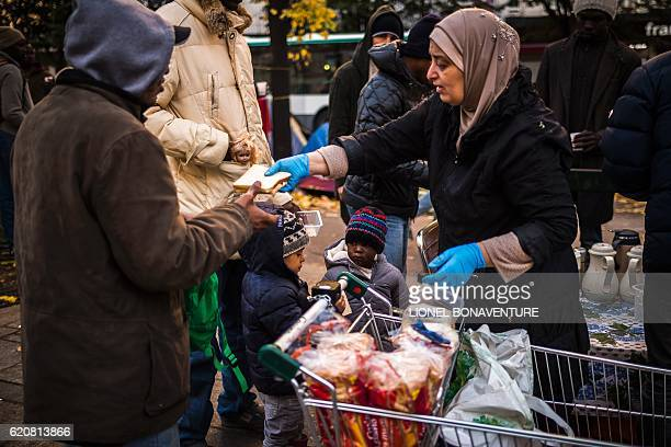 A woman gives food to migrants at a makeshift tent camp near to the Stalingrad metro station one of several camps sprouting up around the French...