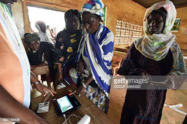 A woman gives her fingerprint to a biometric identification scanner to vote for the Ivory Coast presidential elections at a polling station on...
