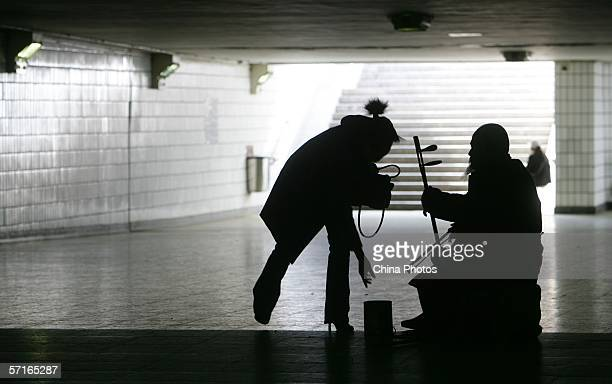 A woman gives money to a beggar in a pedestrian subway on March 23 2006 in Beijing China The State Development and Reform Commission stated last...