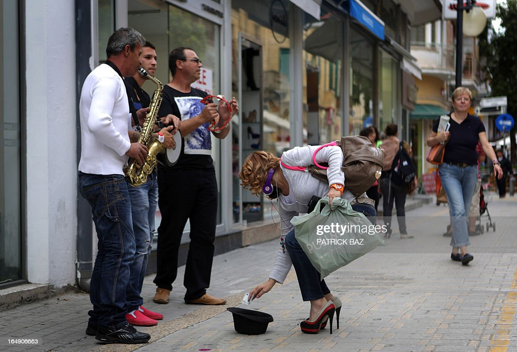 A woman gives money to musicians busking in a street in the old part of the Cypriot capital Nicosia on March 29, 2013. Businesses and families in Cyprus are suffering despite the return to normal banking hours, as draconian capital controls make it hard to pay salaries and bills, trade groups said. AFP PHOTO / PATRICK BAZ