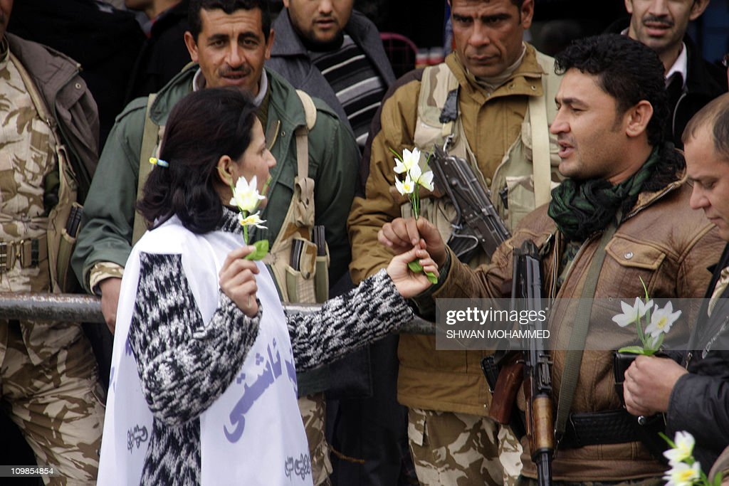 A woman gives out flowers to soldiers as artists and intellectuals form a wall of peace between protesters and security men to prevent violence in Sulaimaniyah's Tahrir Square, (270 km) north of Baghdad, as some 4000 demonstrators take to the streets of the northern city on February 22, 2011, calling for political reforms, an end to corruption and an improvement to conditions in the region.