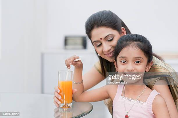 Woman giving a glass of juice to her daughter