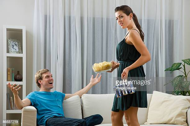 A woman giving a man a bowl of crisps and beer