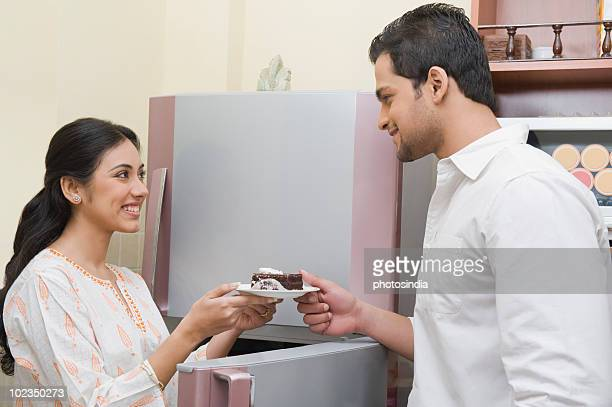 Woman giving a plate of cake to a man in front of a refrigerator