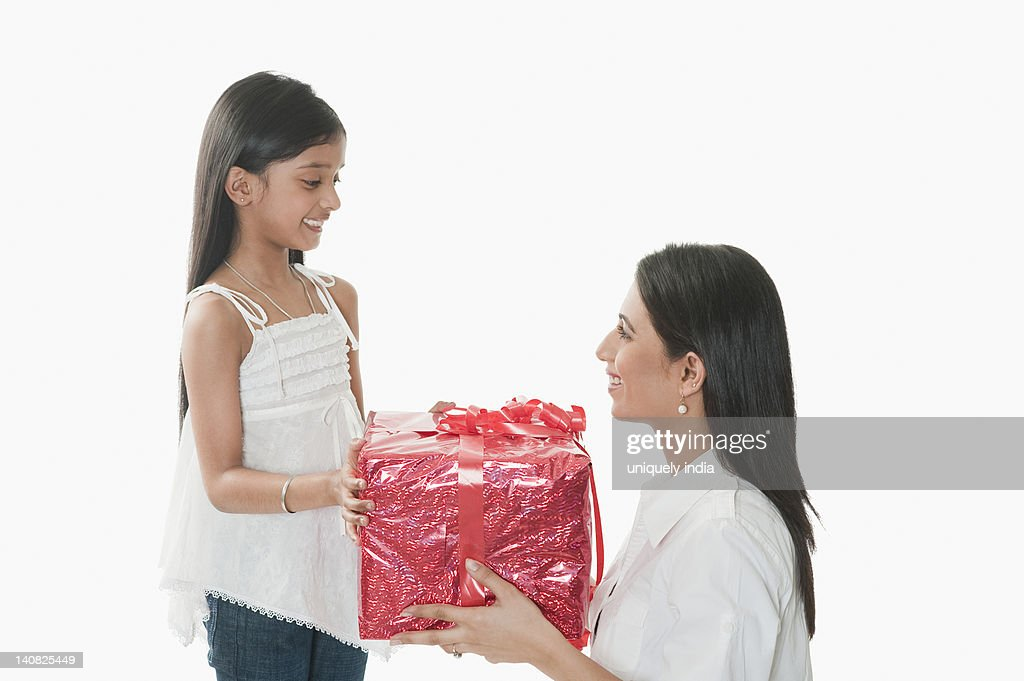 Woman giving a present to her daughter : Stock Photo