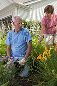 Woman giving advice to her husband about planting flowers in their garden