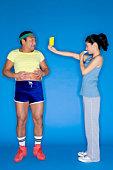 Woman giving an overweight man a yellow card