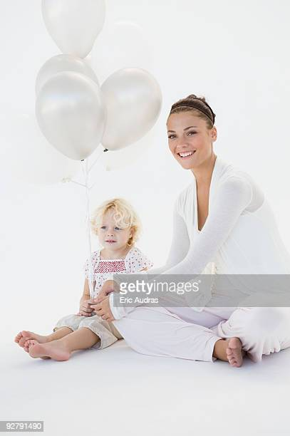 Woman giving balloons to her daughter