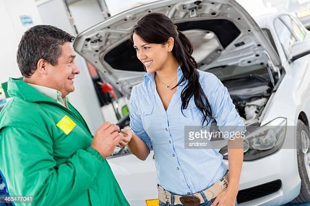 Woman giving car keys to mechanic
