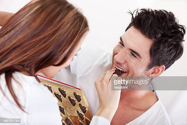Woman giving chocolate candy to a man
