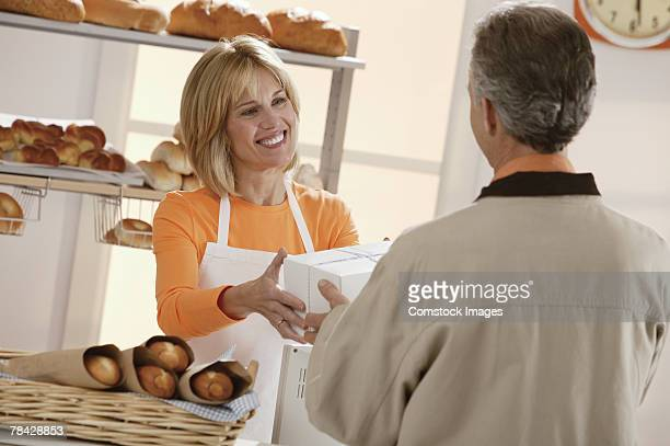 Woman giving customer boxes in bakery