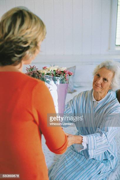 Woman giving flowers to older woman