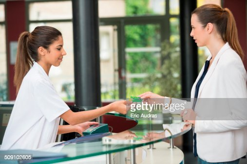 Woman giving french social security card to receptionist at hospital reception desk