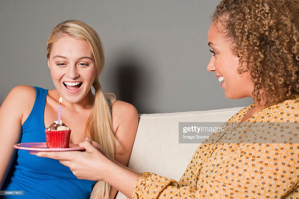 Woman giving friend cupcake : Stock Photo