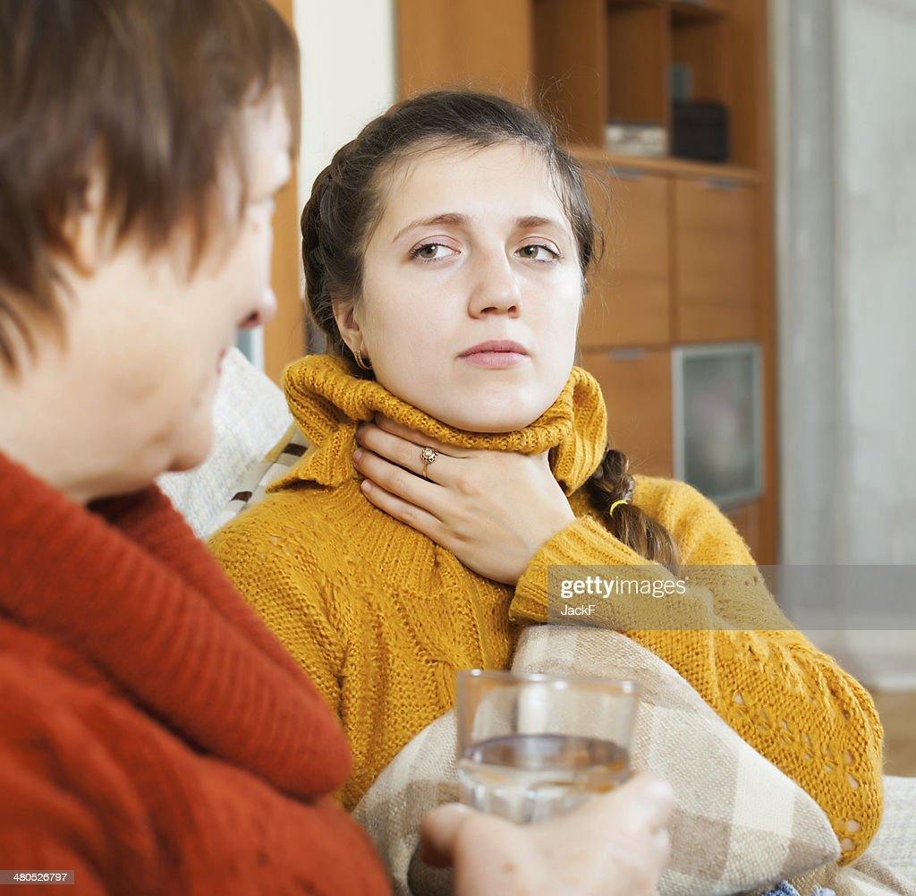 Woman giving glass of water to unwell friend : Stockfoto