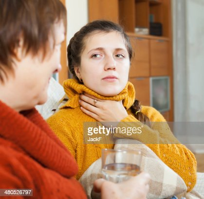 Woman giving glass of water to unwell friend : Stock Photo