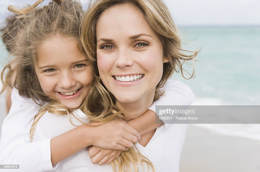 Woman giving her daughter piggyback on the beach : Stock Photo