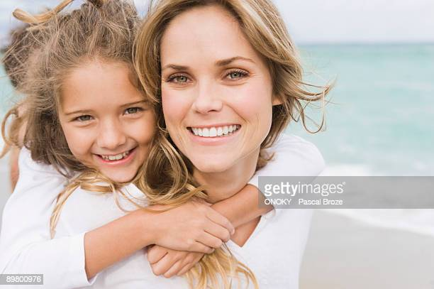 Woman giving her daughter piggyback on the beach