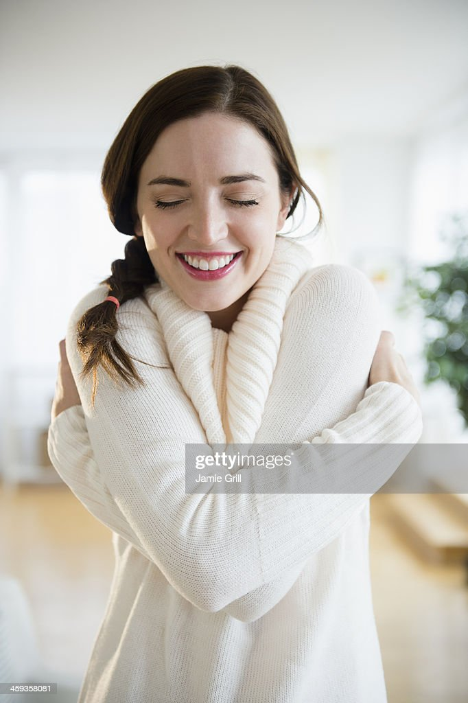 Woman giving herself a hug, smiling : Stock Photo