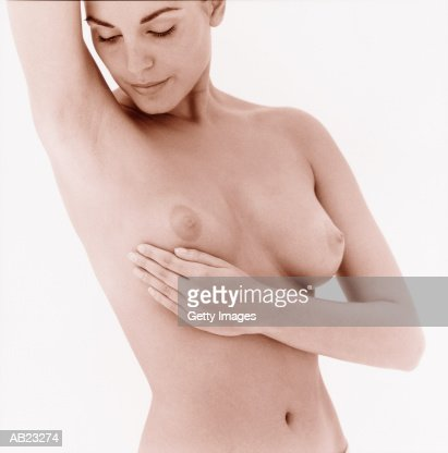 Woman giving herself breast examination : Stock Photo