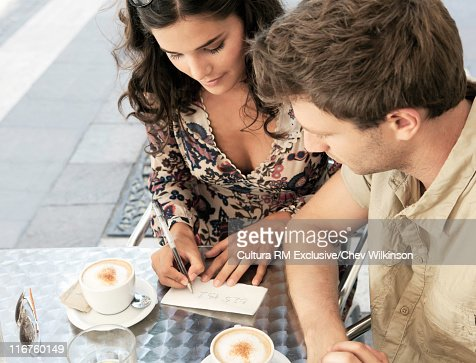 Woman giving man her phone number : Stock Photo