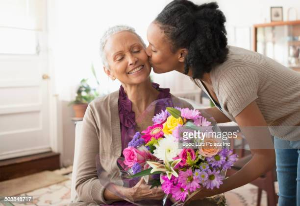 Woman giving mother bouquet of flowers