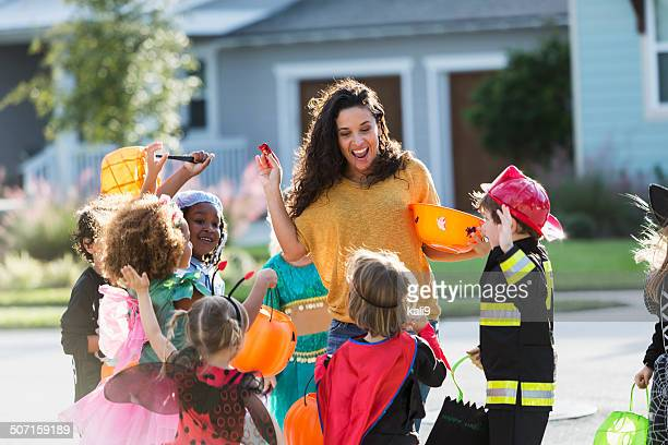 Woman giving out candy to group of children on halloween