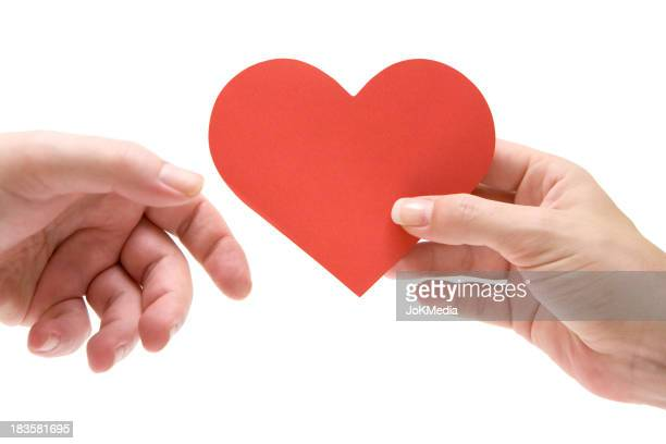 Woman giving paper heart to man