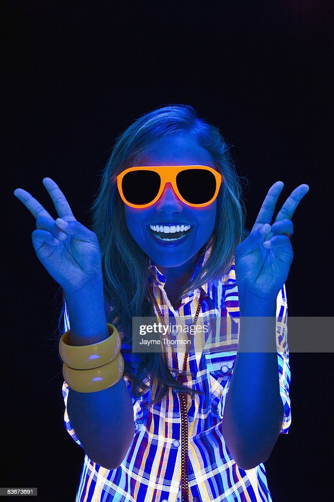Woman giving peace sign under blacklights