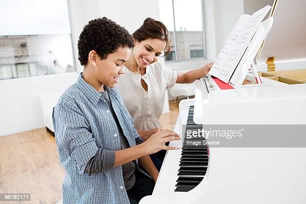 Woman ギブピアノのレッスンに少年