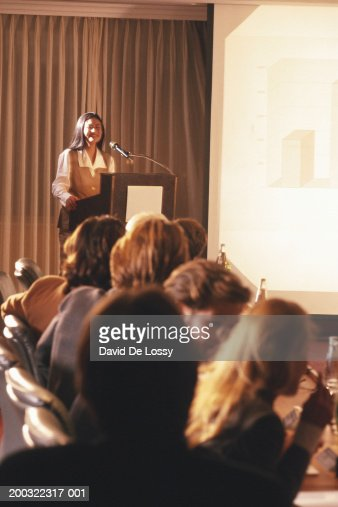 Woman giving presentation to group of business people : Stock Photo