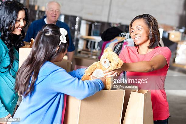 Woman giving teddy bear to needy family at donation center