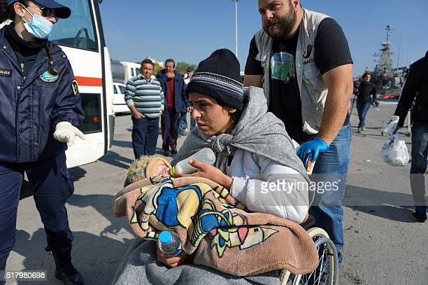 A woman giving the bottle to her baby waits along with other migrants and refugees to board buses taking them to the registration hotspot of Moria...
