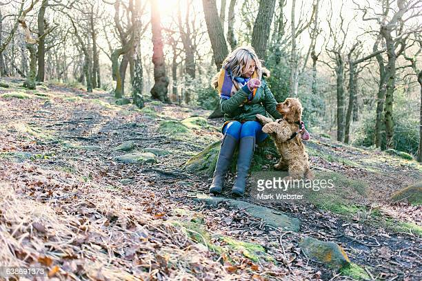Woman giving treat to puppy in forest