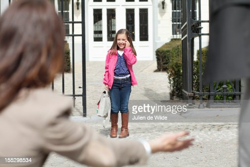 Woman giving warm welcome to her daughter at the school gate
