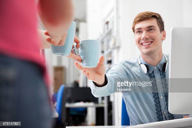 Woman giving young man coffee in office
