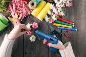 Woman glue handmade flowers with melt gun. Top view