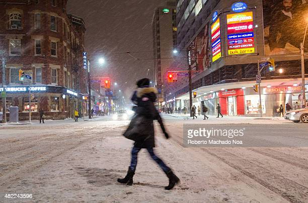 Woman goes snowcovered road in the city in the evening City under snowstorm City lights shine showcases